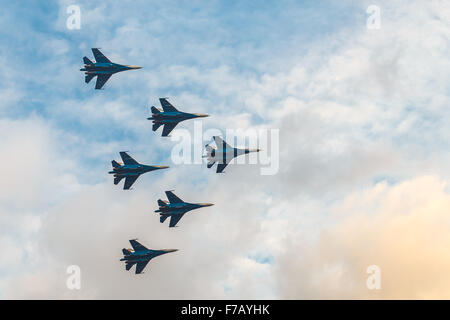 Silhouettes of russian fighter aircrafts SU-27 in the cloudy sky - Stock Photo