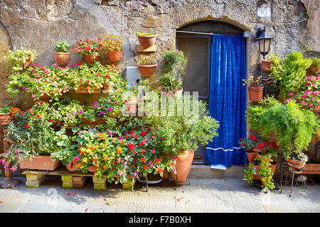 City street decorated with flowers, Pitigliano, Tuscany, Italy - Stock Photo