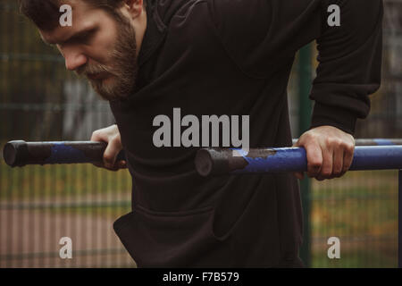 Muscular man during his workout on the street - Stock Photo