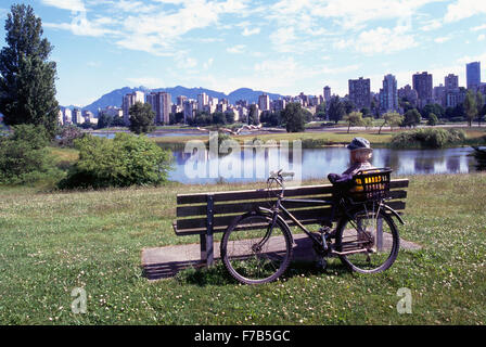 Vancouver, BC, British Columbia, Canada - Cyclist sitting on Bench in Vanier Park and admiring View of City's West - Stock Photo