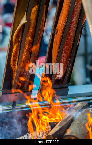 Salmon is smoked and grilled over open fire, specialty on a food market - Stock Photo