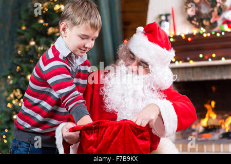 Santa Claus giving a present from sack to child boy near the fireplace and Christmas tree at home. - Stock Photo