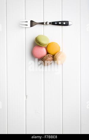 sweet french macarons on white kitchen table - Stock Photo