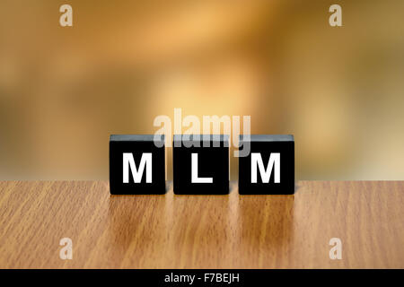 MLM or Multi Level Marketing on black block with blurred background - Stock Photo