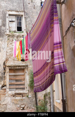 A back street in Corfu Town with colourful washing hanging out to dry in the street. Corfu - Stock Photo