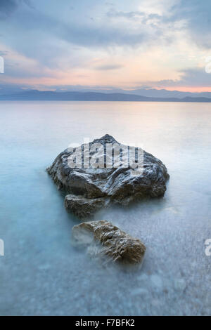 The pebbles and rocks on Kanoni beach, Kassiopi, Corfu are surrounded by the incoming tide. - Stock Photo