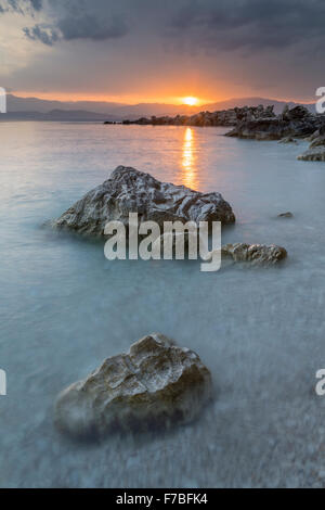 The pebbles and rocks on Bataria beach, Kassiopi, Corfu are lit up with the strong orange light of sunrise. - Stock Photo