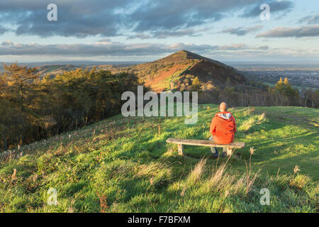 A walker in a bright orange coat sits on a wooden bench on Jubillee Hill to watch the beautiful sunset lighting - Stock Photo