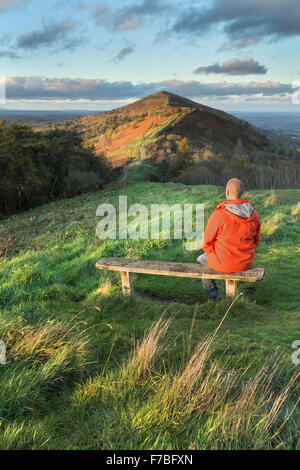 A walker in a bright orange coat sits on a wooden bench on Jubillee Hill to watch the beautiful sunset. - Stock Photo