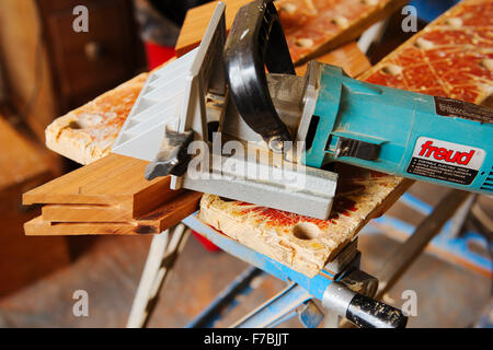 A biscuit jointer for cutting slots in a mitred wooden frame held in a workmate for jointing - Stock Photo