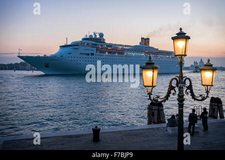 Venice, Italy,  cruise ship, Costa Classic, leaving at sunset with tourists standing on deck - Stock Photo