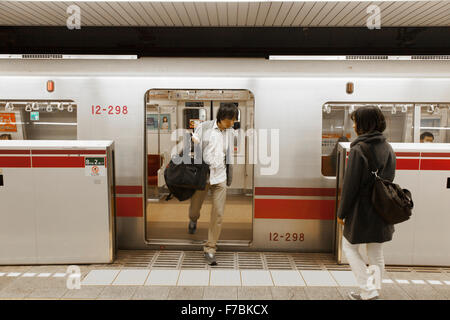 People getting on and off at a Tokyo subway - Stock Photo