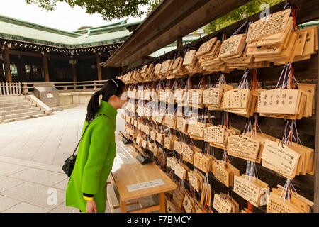 A girl reading the prayers at the Shinto shrine in Tokyo - Stock Photo
