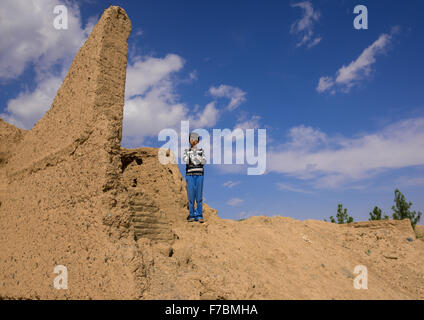 An Afghan Refugee Boy Standing On House Ruins In A Village, Isfahan Province, Kashan, Iran - Stock Photo