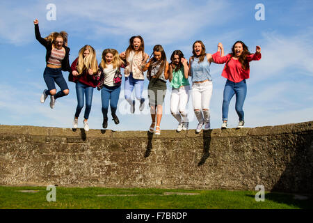 Eight teenage girls holding hands and jumping off the Broughty Ferry Castle wall in Dundee, UK - Stock Photo