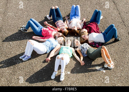 Eight sleeping teenage girls lying together in a circle close to the waters edge near Broughty Ferry Castle in Dundee, - Stock Photo