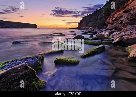 Transparent clear sea floor at Royal National Park Wattamola rocky beach in Australia at sunrise with blurred water - Stock Photo