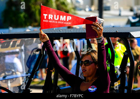 Hispanic woman holding a pro-Trump pennant showing her support by wearing t-shirts at his Presidential candidacy - Stock Photo