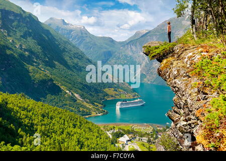 Tourist standing on the rock cliff, cruise ship in Geiranger Fjord in the background, Norway - Stock Photo