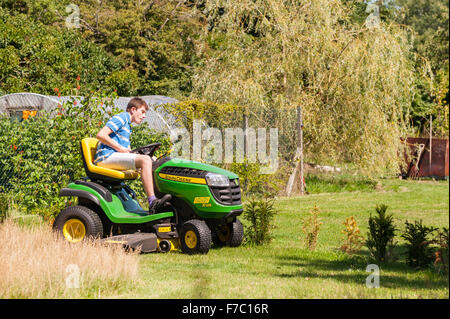 A 15 year old boy mowing the lawn on a John Deere ride on mower in the Uk - Stock Photo