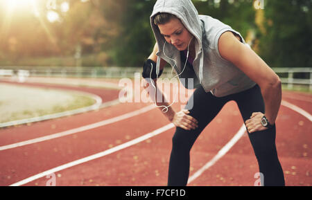 Young sportswoman standing on stadium and listening to music, looking down - Stock Photo