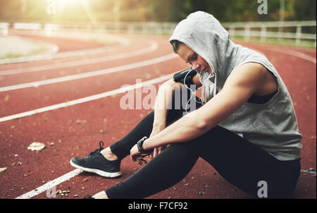 Young woman in sportswear sitting on stadium, listening to music and preparing for training - Stock Photo