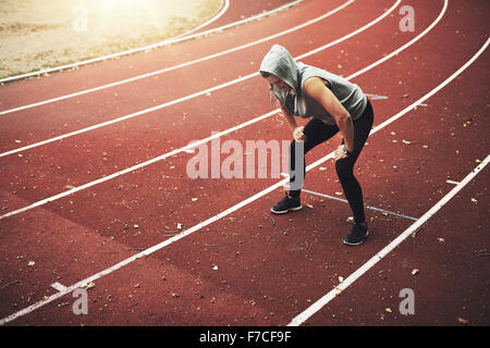 Young female runner standing on stadium and listening to music, relaxing after running - Stock Photo