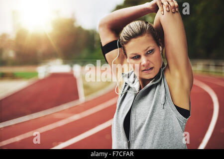 Fit young woman stretching her arms before training. Concentrated - Stock Photo