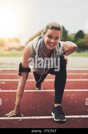 Young blonde sportswoman looking at camera while stretching on stadium before running, listening to music - Stock Photo