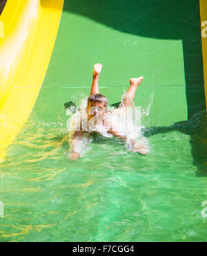 child playing on water slide at amusement park - Stock Photo