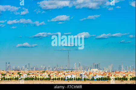 Skyline of Dubai with modern luxury villas at The Villa residential housing development in foreground in United - Stock Photo