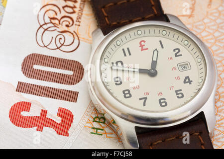 Wristwatch clock face on a British Sterling £10 ten pound note GBP to illustrate time is money concept. England - Stock Photo