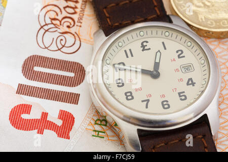 Wristwatch on a ten pound note and a coin to illustrate time is money concept. England, UK, Britain - Stock Photo