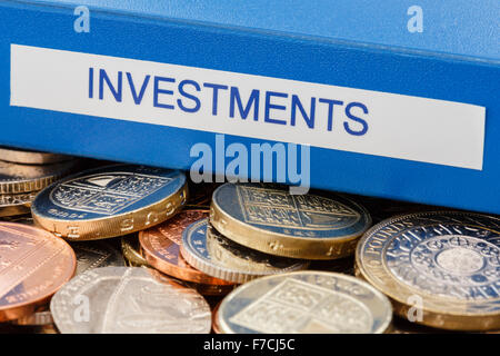 Investments folder on a pile of English sterling old £ pound coins to illustrate investing money in stocks and shares - Stock Photo