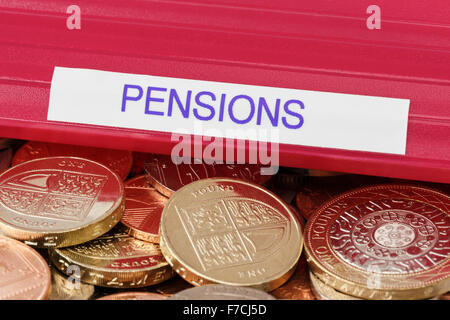 Pensions portfolio on a pile of sterling pound coins to illustrate investing money for retirement planning and pension - Stock Photo