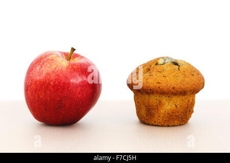 Rosy red apple healthy food option and a muffin cake unhealthy snack on a tabletop to illustrate alternative foods - Stock Photo