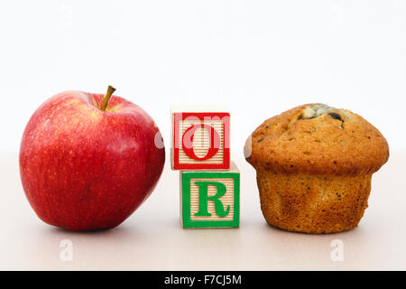 Rosy red apple and a muffin cake with word OR in letter blocks on a tabletop to illustrate choice of healthy or - Stock Photo