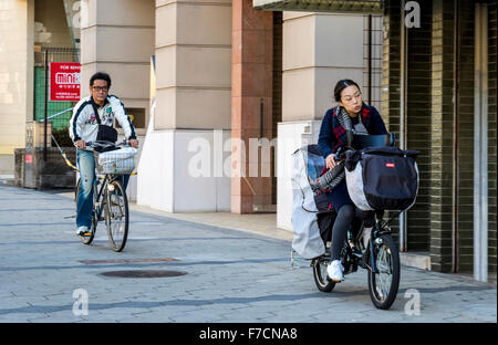 Cycling in the city of Osaka Japan along one of the many cycle paths which is kept separate from road traffic - Stock Photo