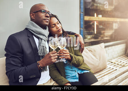 Romantic loving couple enjoying each others company sitting relaxing on a wooden restaurant bench in a close embrace - Stock Photo