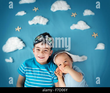 Two boys lying on blanket with white clouds - Stock Photo
