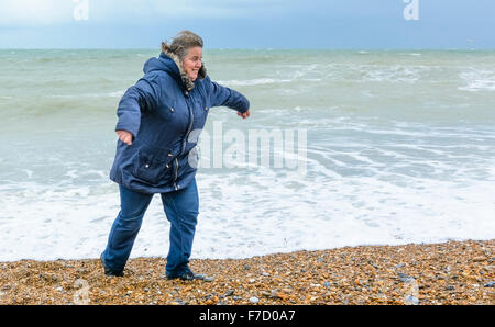 Middle aged woman on a beach running from waves in the UK. - Stock Photo