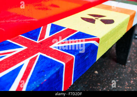 A bench painted with the British Union Flag and Irish Tricolour, with a toxic radioactive zone between. - Stock Photo