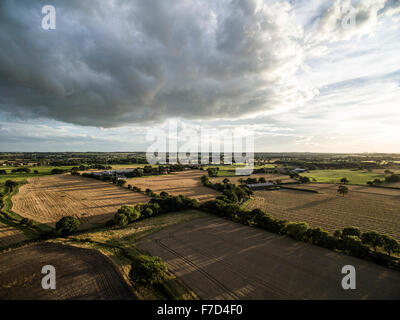 Aerial view of patchwork quilt fields, horizon and dramatic clouds and blue sky above - Stock Photo