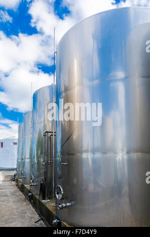 Stainless steel fermenting vats at a vineyard. - Stock Photo
