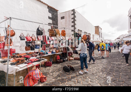 Handbags, jewelry and leather goods for sale at a stall in the the Sunday Market in the Lanzarote town of Teguise - Stock Photo