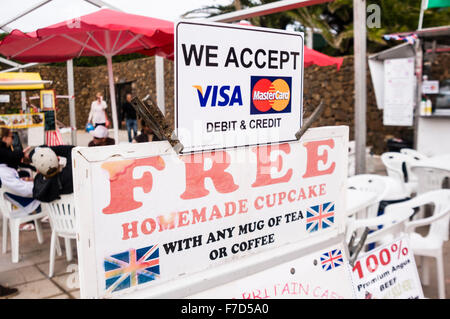 Sign at a Spanish market advertising British English food and free homemade cupcakes with any mug of tea or coffee. - Stock Photo