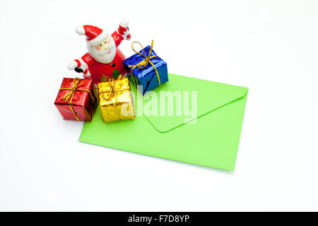 Green closed christmas card with presents and Santa Claus figurine - Stock Photo