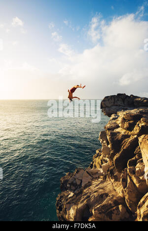 Cliff Jumping into the Ocean at Sunset, Summer Fun Lifestyle - Stock Photo