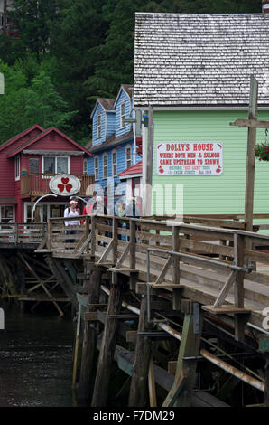 Tourist enjoy a visit to the boardwalk on Creek Street.  Gold and souvenir shops reside in remodeled houses of prostitution. - Stock Photo