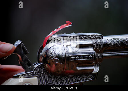 Close up of a child's silver old west toy cap gun with strip of caps coming out of the top of the gun. - Stock Photo
